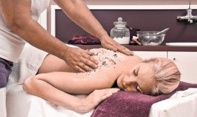 Blonde Frau liegt auf dem Bauch und bekommt eine Salzmassage