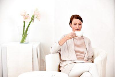 Dunkelhaarige Frau sitzt auf einem Sessel und trinkt Tee