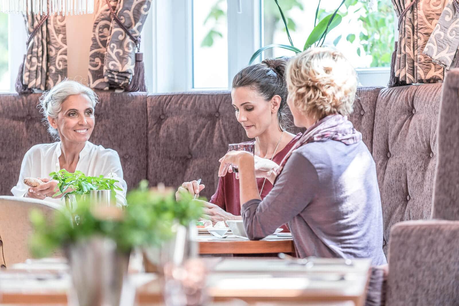 3 Frauen sind beim Essen und unterhalten sich