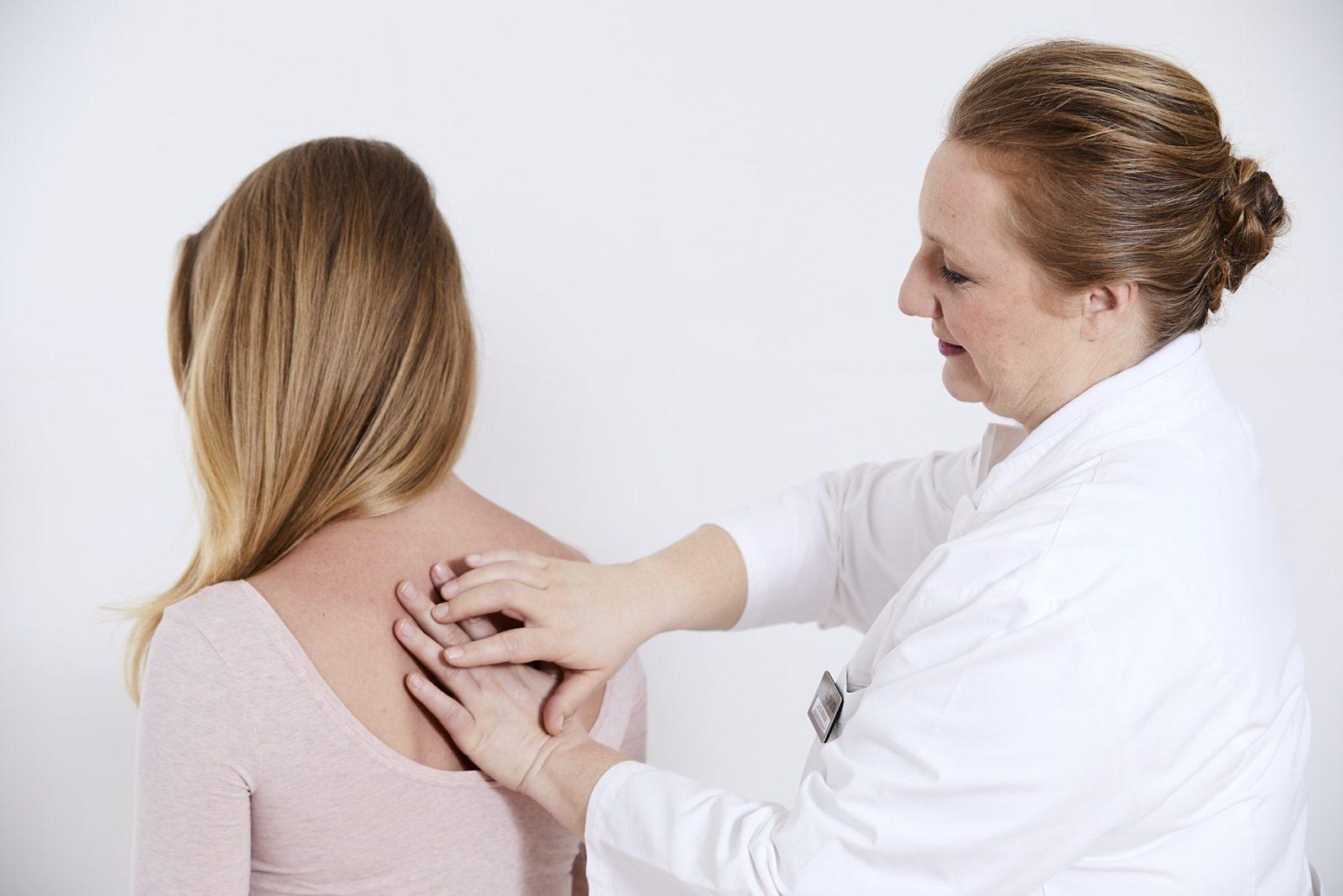 Ärztin behandelt Patienten am oberen Rücken