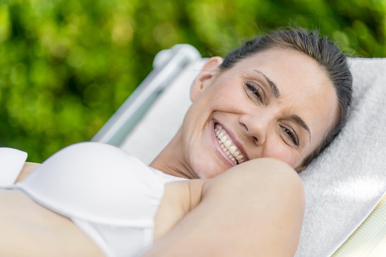 Glückliche Frau liegt auf einer Liege