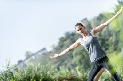 Dunkelhaarige Frau macht Yoga im Garten von la pura