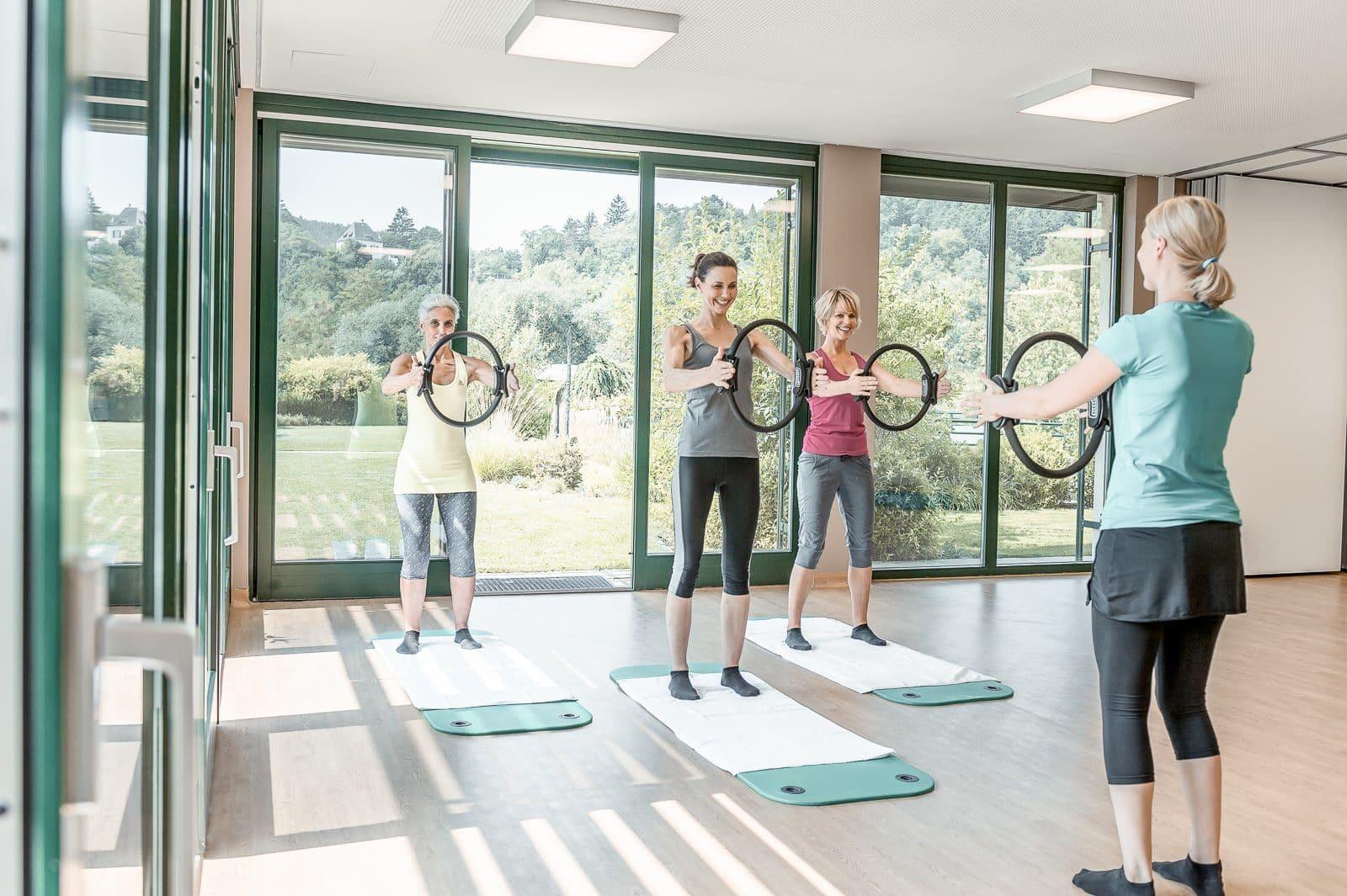3 Frauen machen unter Anleitung Gymnastik mit Ringen