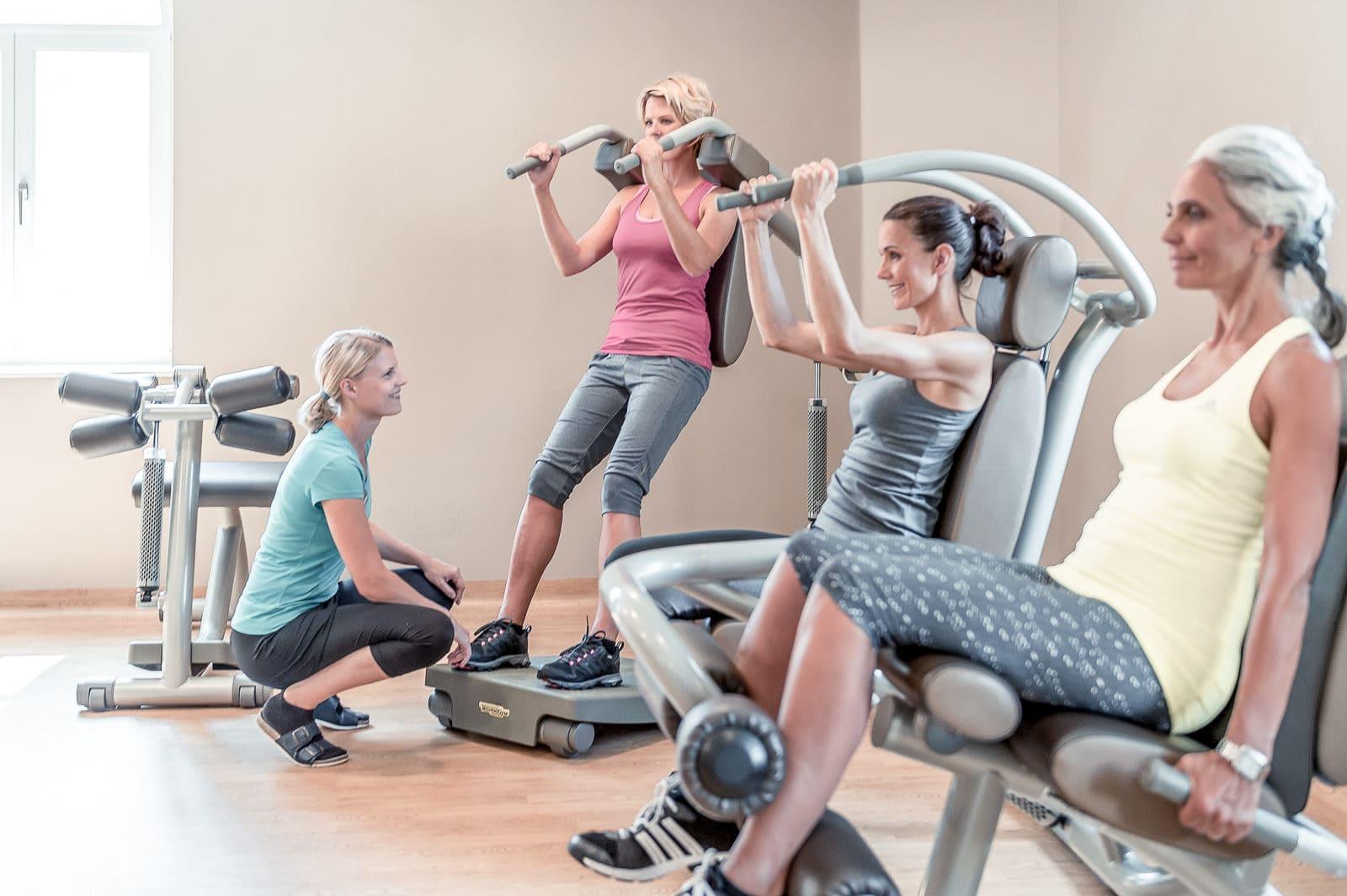 3 Frauen trainieren unter Anleitung an Fitnessgeräten