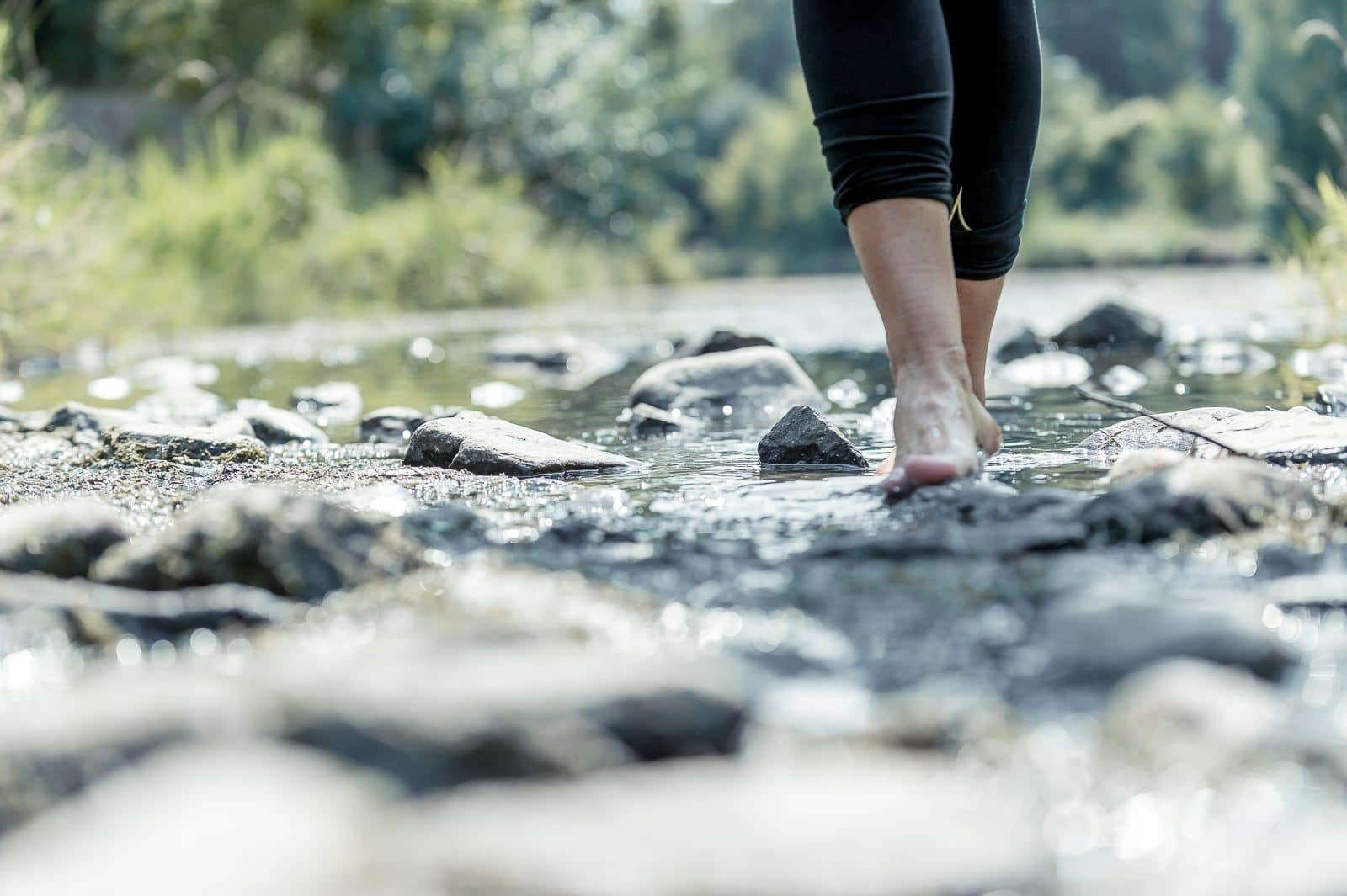 Frau läuft Barfuß durch Flussbett
