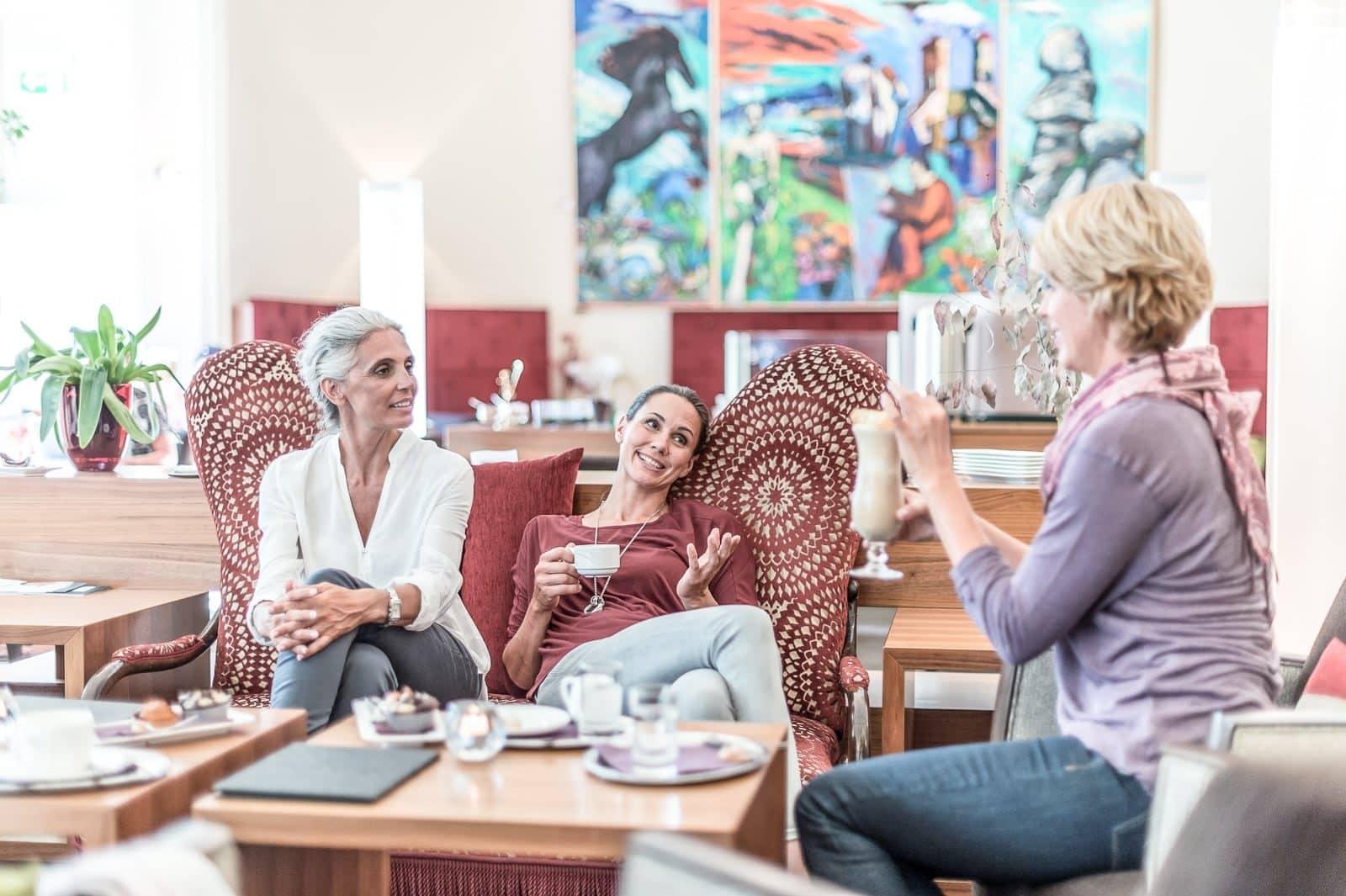 3 Frauen sitzen in der Lobby und trinken Tee