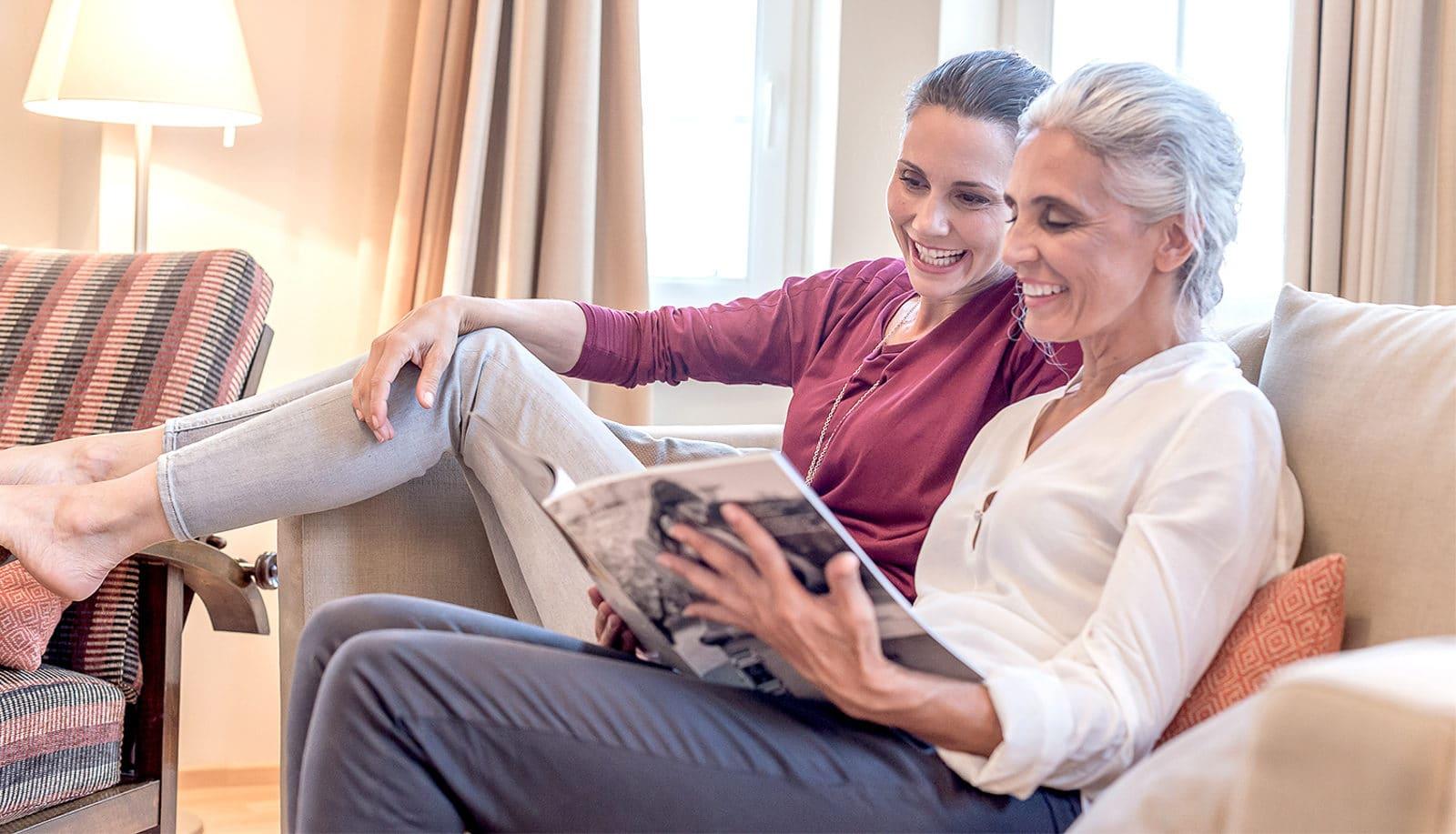2 Frauen sitzen auf dem Sofa und lesen gemeinsam ein Magazin