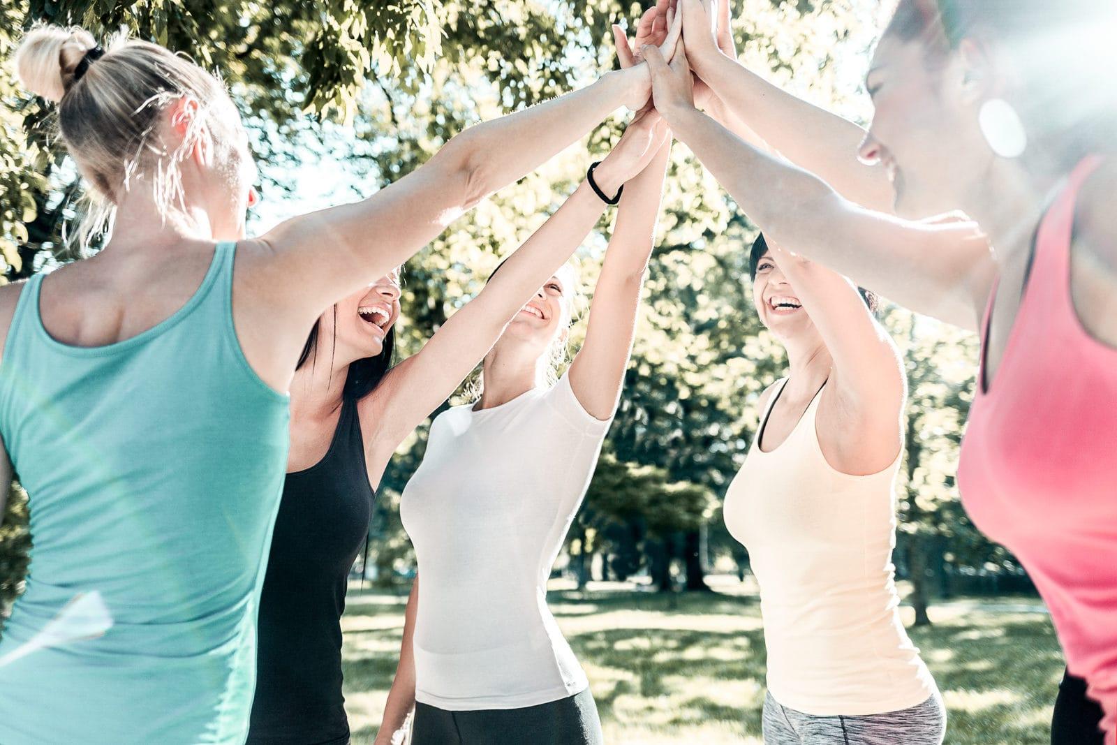 5 Frauen stehen im Kreis und geben sich ein high five