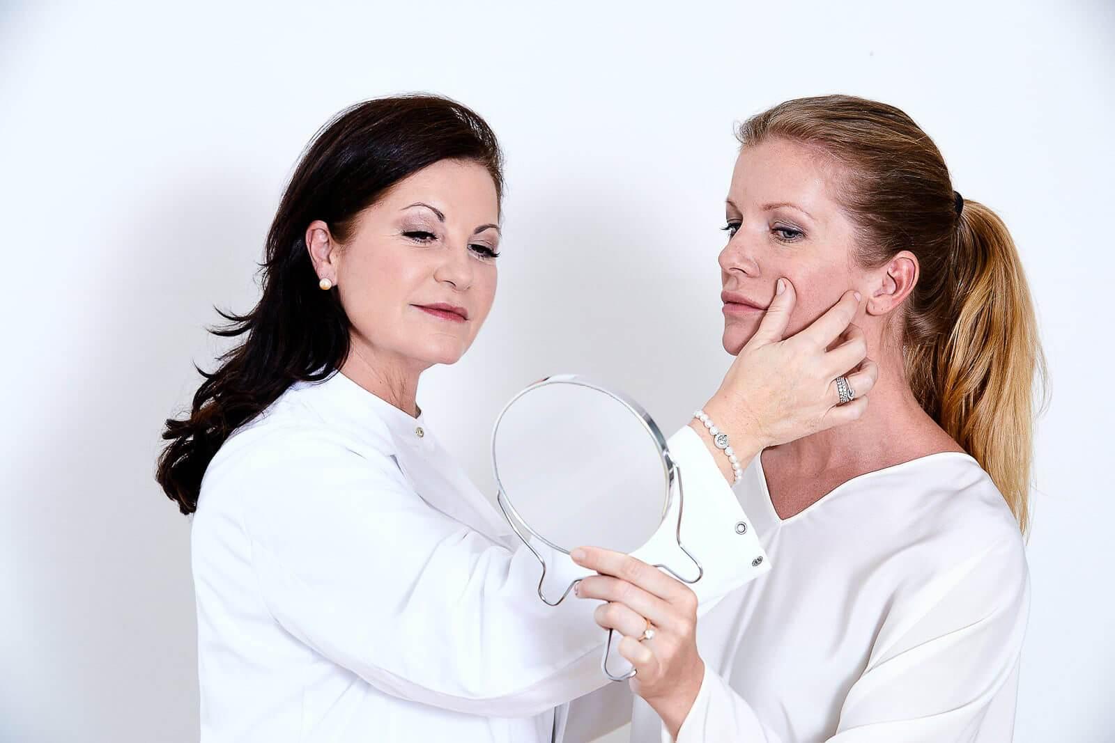Frau schaut in Handspiegel und Ärztin gibt Schönheitsberatung