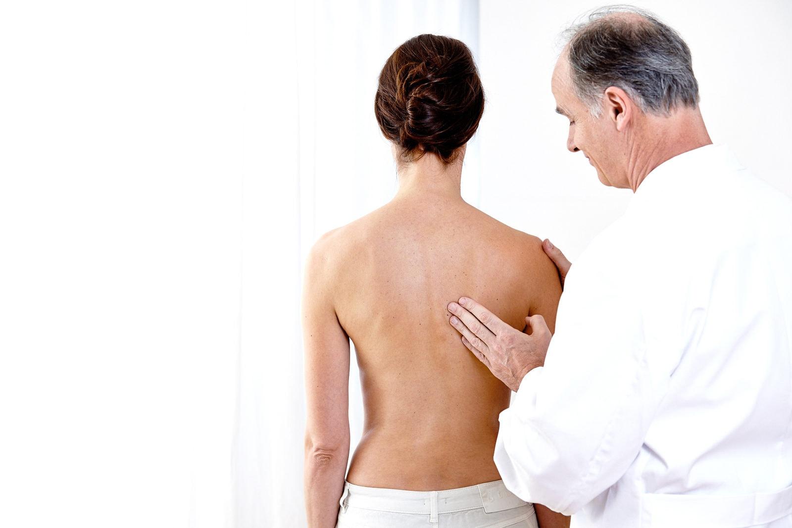 Patientin bekommt im Stehen eine Wirbelsäulenbehandlung vom Arzt