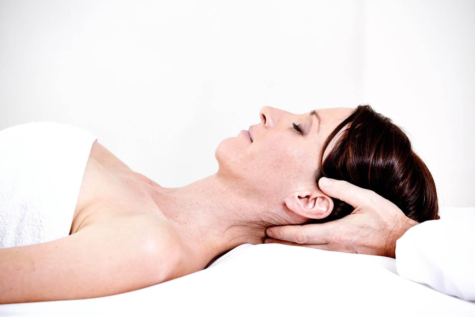 Dunkelhaarige Frau bekommt eine Nackenmassage