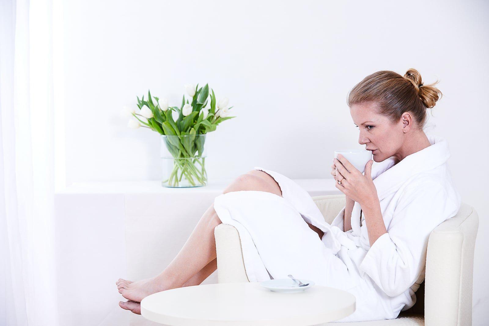 Blonde Frau sitzt mit Bademantel auf Sessel und trinkt Tee