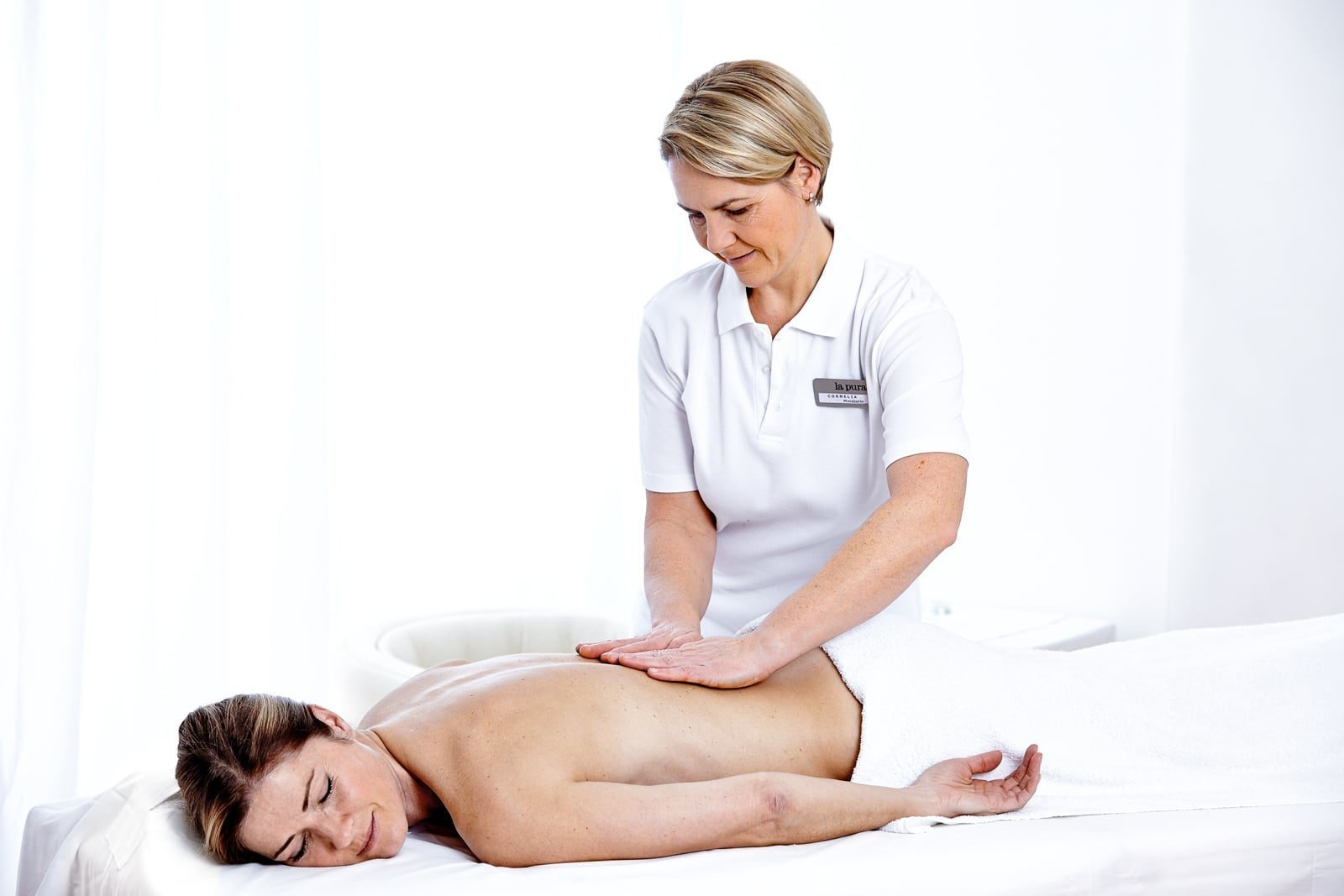 Eine Dame bekommt eine Rückenmassage