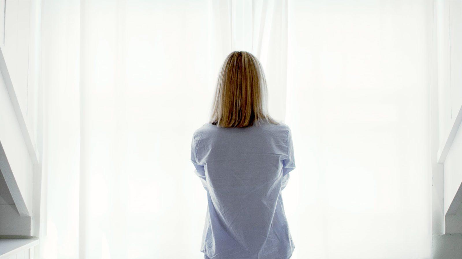 Blonde Frau im Nachthemd öffnet die Gardinen
