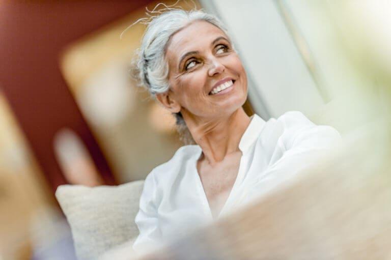 Lächelnde Dame sitzt auf einem Sessel und schaut dabei nach rechts