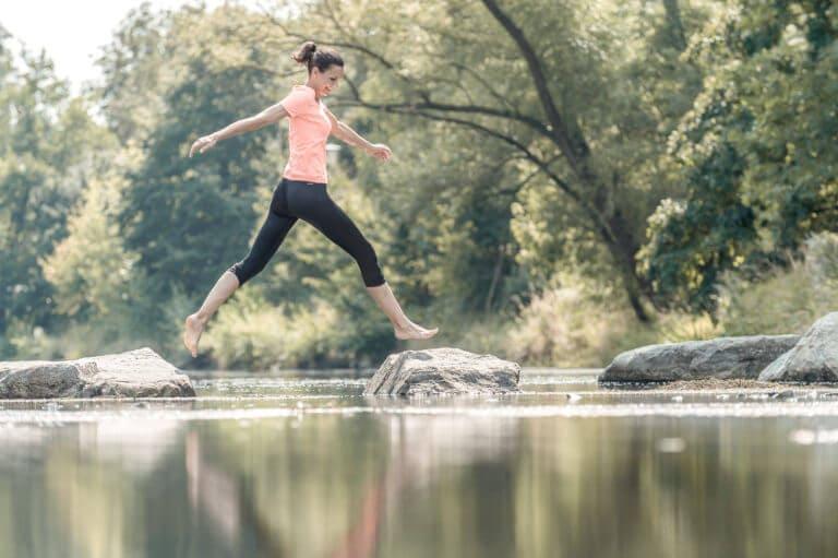 Frau in Trainingskleidung springt von Stein zu Stein über einen Bach