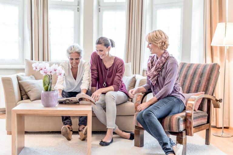 3 Damen verschiedenen Alters sitzen auf einer Couch und schauen eine la pura Broschüre an