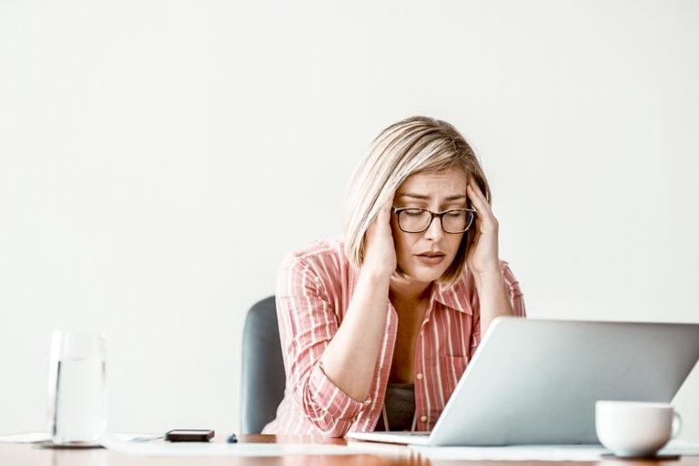 Gestresste Frau mit Brille sitzt vor Laptop