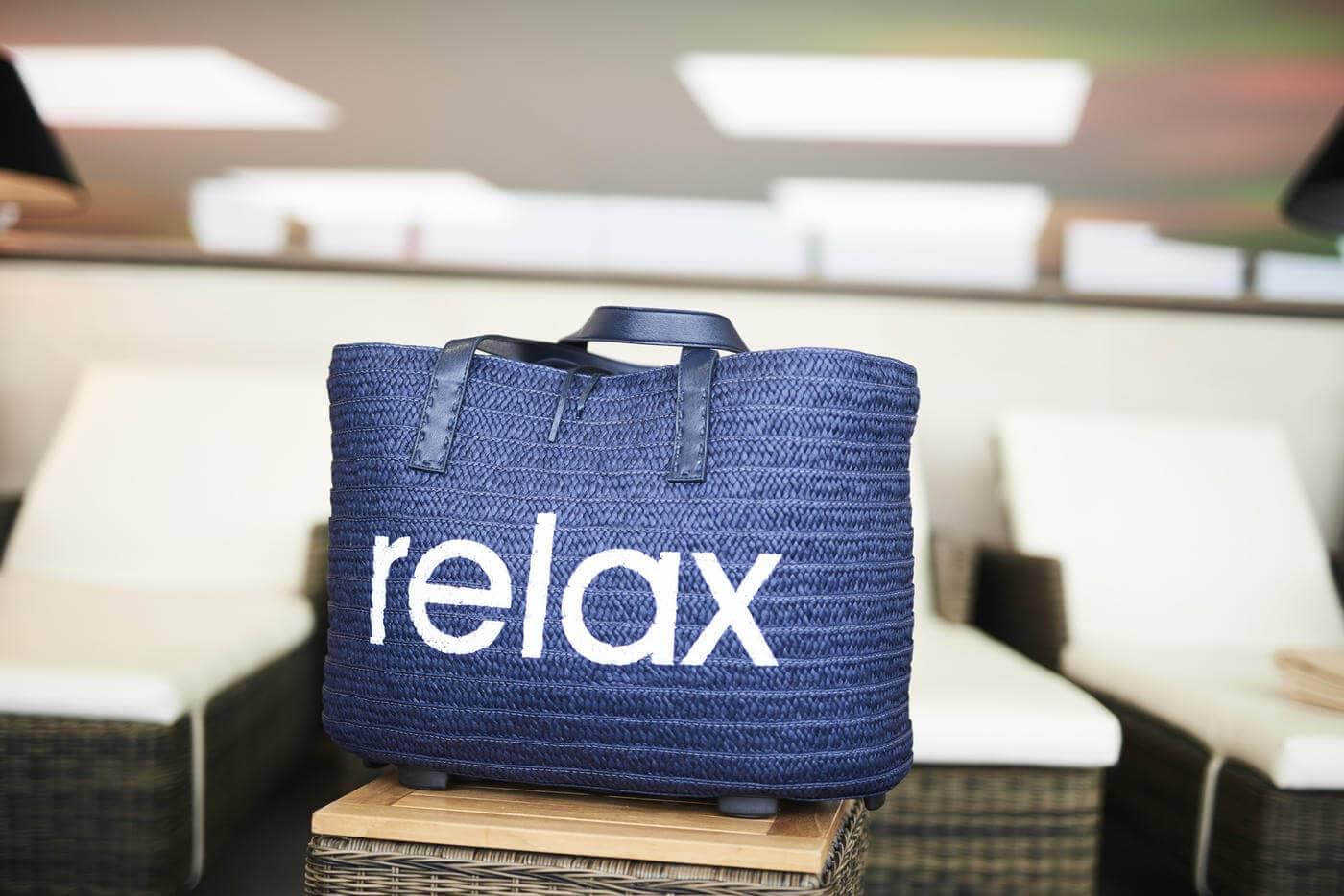 Blaue Tasche mit weißem Relax Aufdruck wurde vor Liegen platziert